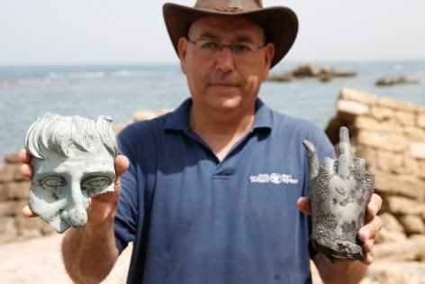 An Israel Antiquities Authority (IAA) employee holds parts of statues, which the IAA estimates to be around 1600 years old, after they were recovered from a merchant ship in the ancient harbor of the Caesarea National Park May 16, 2016. REUTERS/ Baz Ratner