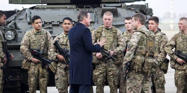 RUISLIP, ENGLAND - NOVEMBER 23: British Prime Minister David Cameron talks with soldiers from the Royal Welsh Infantry as they stand in front of a Lockheed Martin Warrior Infantry Fighting Vehicle during his visit to Royal Air Force station RAF Northolt at RAF Northolt on November 23, 2015 in Ruislip, England. According to a government statement Mr Cameron is set to promise an additional 12 billion GBP to strengthen the defence forces, when he presents his government's Strategic Defence and Security Review to parliament later today. (Photo by Jack Hill - WPA Pool/Getty Images)