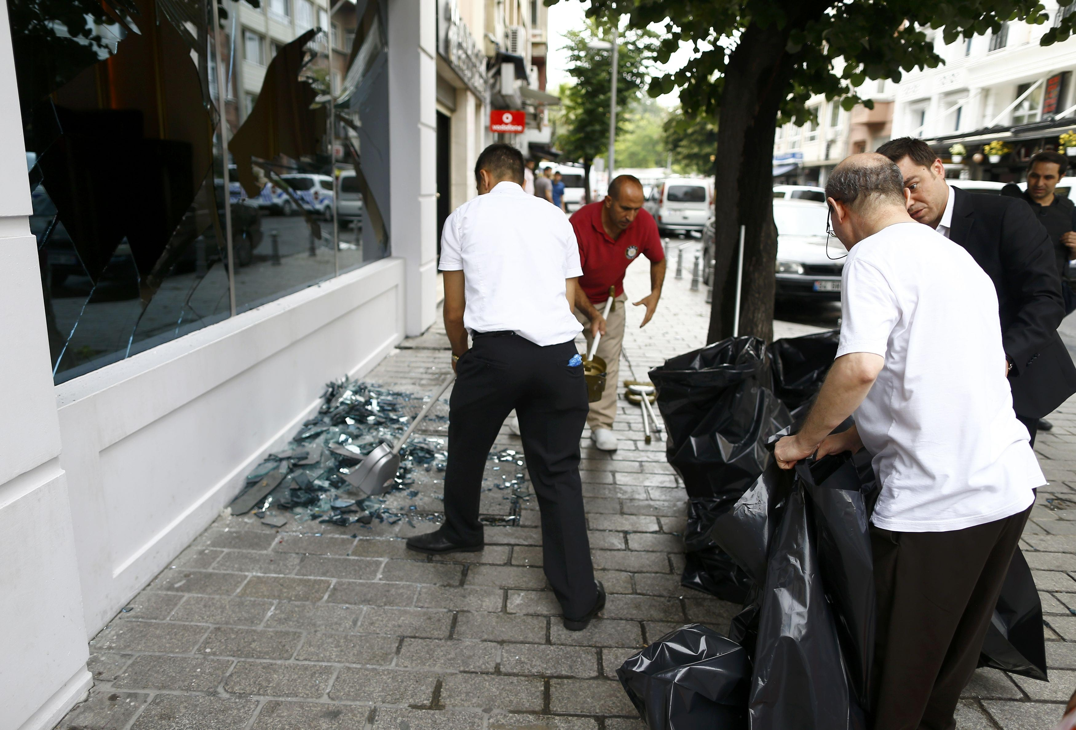 People remove glass of a destroyed shop window near the site where a Turkish police bus was targeted in a bomb attack in a central Istanbul district, Turkey, June 7, 2016. REUTERS/Osman Orsal