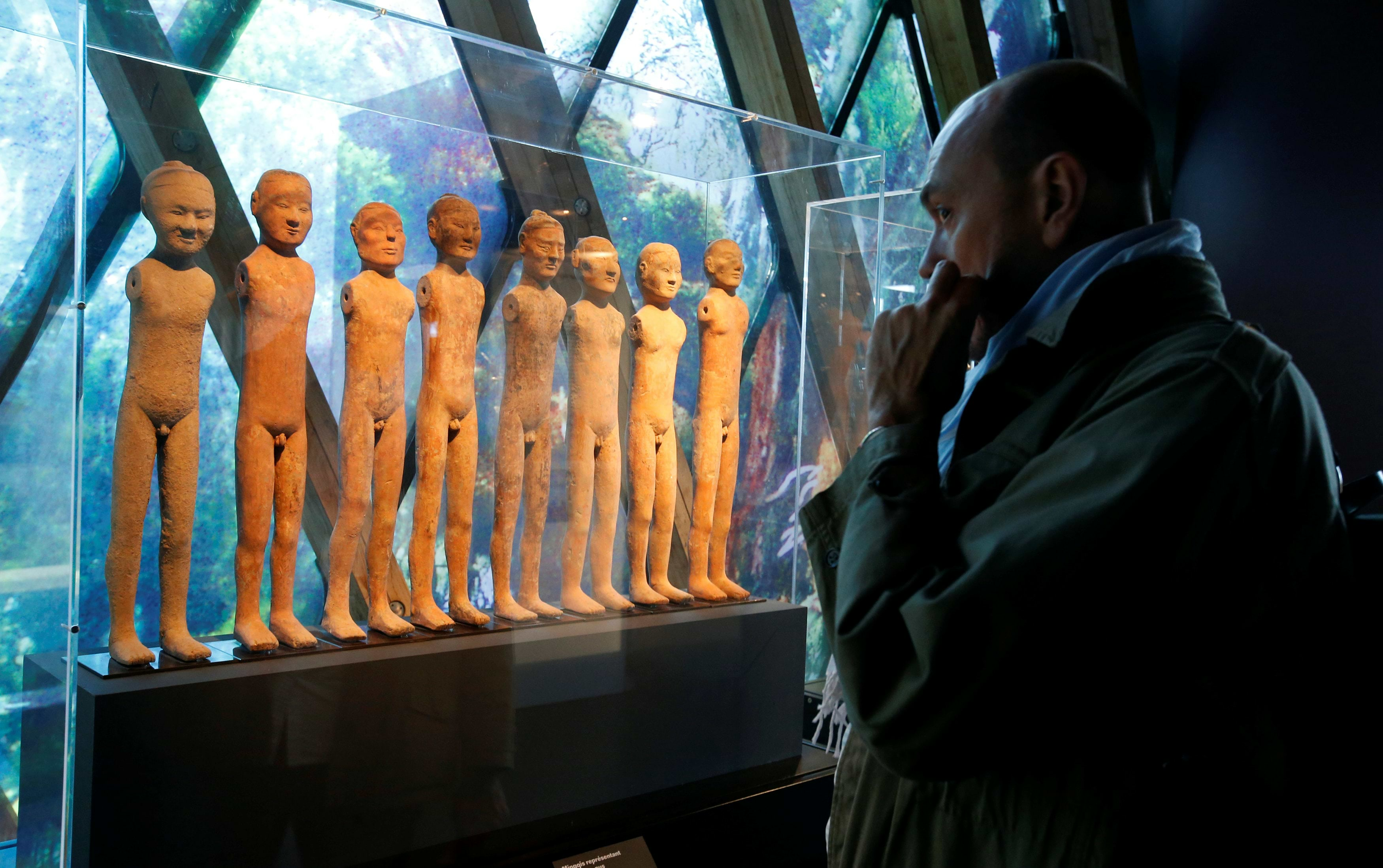 "A visitor looks at Mingqi figurines (Western Han period) during a press visit of the exhibition ""Jacques Chirac ou le dialogue des cultures"" at the Musee du quai Branly in Paris, France, June 20, 2016. This major exhibition is devoted to former French President Chirac, the Quai Branly Museum founder, who was passionate about non-European arts and different civilizations. REUTERS/Jacky Naegelen"