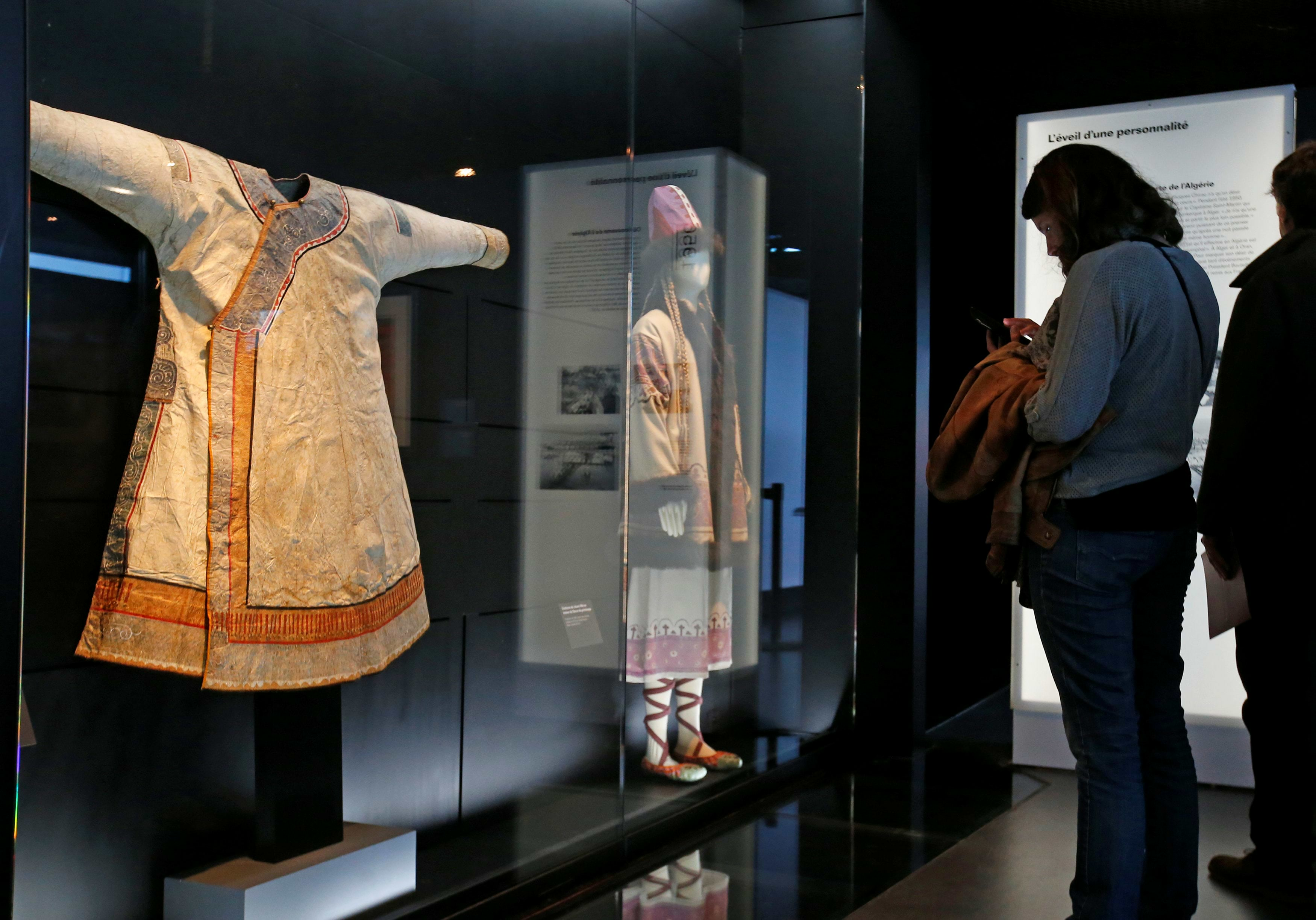 "A visitor looks at a Nivkh tribe dress during a press visit of the exhibition ""Jacques Chirac ou le dialogue des cultures"" at the Musee du quai Branly in Paris"
