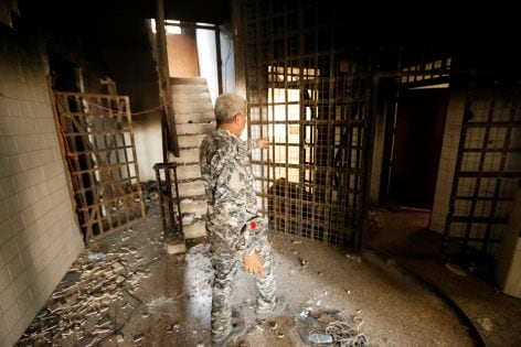 A member of Iraqi government forces walks inside a burnt out prison cell belonging to Islamic State militants in Falluja after government forces recaptured the city from Islamic State militants, Iraq