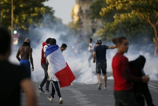 """Tear gas floats in the air during clashes near the Paris fans zone during the Portugal v France EURO 2016 final soccer match, at the Eiffel Tower in Paris, France, July 10, 2016. French police fired tear gas to disperse dozens of people trying to enter the """"fan zone"""" at the foot of the Eiffel Tower to watch the final of the Euro 2016 soccer tournament on Sunday evening, to prevent overcrowding. REUTERS/Stephane Mahe"""