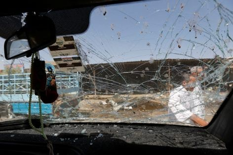 Residents are seen through a shattered windshield of a vehicle damaged at the site of car bomb attack in Rashidiya, a district north of Baghdad