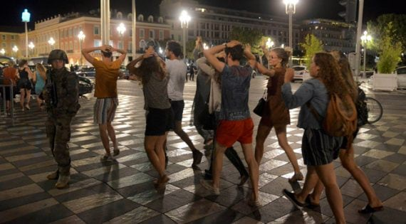 People cross the street with their hands on thier heads as a French soldier secures the area July 15, 2016 after at least 60 people were killed along the Promenade des Anglais in Nice, France, when a truck ran into a crowd celebrating the Bastille Day national holiday July 14. REUTERS/Jean-Pierre Amet TPX IMAGES OF THE DAY