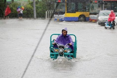 A man rides through a flooded street during a heavy rainfall in Shilipu, Chaoyang Road, Beijing, China, July 20, 2016. REUTERS/Jason Lee