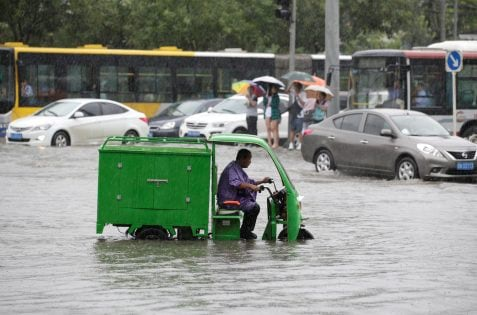 A man rides along a flooded street during a heavy rainfall in Shilipu, Chaoyang Road, Beijing, China July 20, 2016. REUTERS/Jason Lee