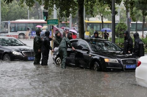 Police and paramilitary police help to remove a car trapped on a flooded street during a heavy rainfall in Shilipu, Chaoyang Road, Beijing, China July 20, 2016. REUTERS/Jason Lee