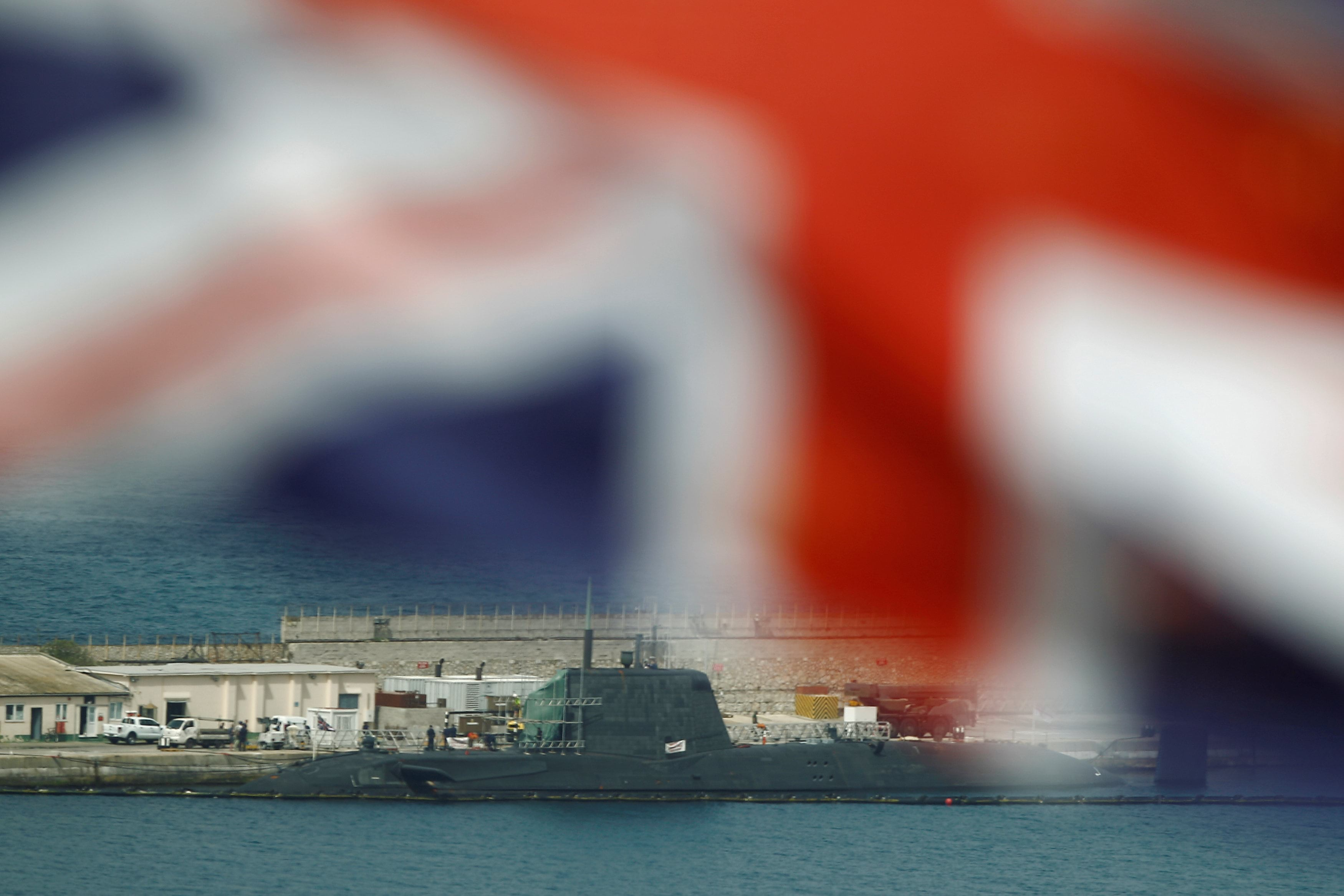 "The Union Jack is seen flying while a British nuclear Astute-class submarine HMS Ambush is seen docked in a port while it is repaired after it was involved in a ""glancing collision"" with a merchant vessel off the coast of the peninsula of Gibraltar on Wednesday, in the British overseas territory of Gibraltar, July 21, 2016. REUTERS/Jon Nazca"