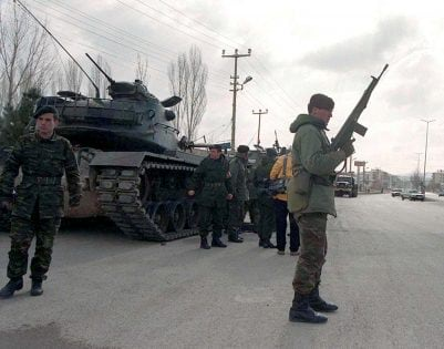 A Turkish soldier stands guard near tanks and armoured vehicles paraded through the main street of Sincan, a district near capital Ankara, Turkey, in this file photo taken on February 4, 1997. REUTERS/File photo