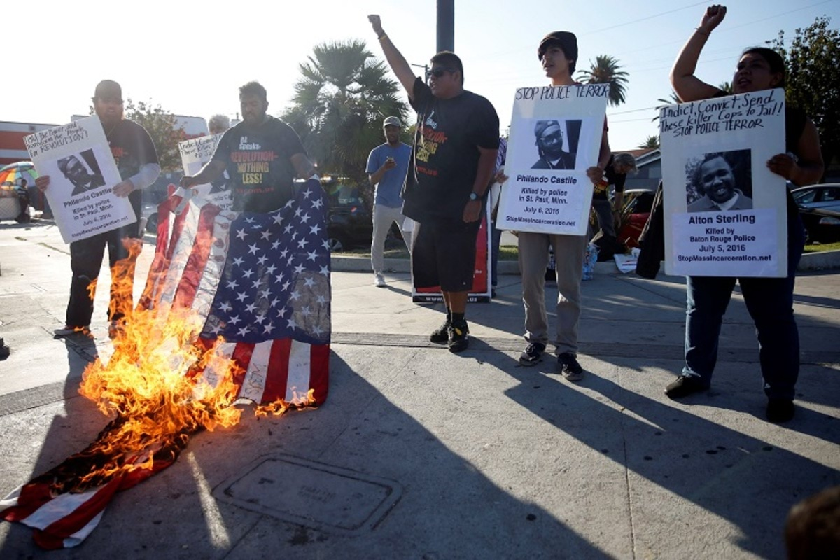 Activists burn a flag while protest on the corner of Florence Ave and Normandie Ave against the police shootings that lead to two deaths in Louisiana and Minnesota, respectively, in Los Angeles, California, U.S. July 7, 2016. REUTERS/Patrick T. Fallon