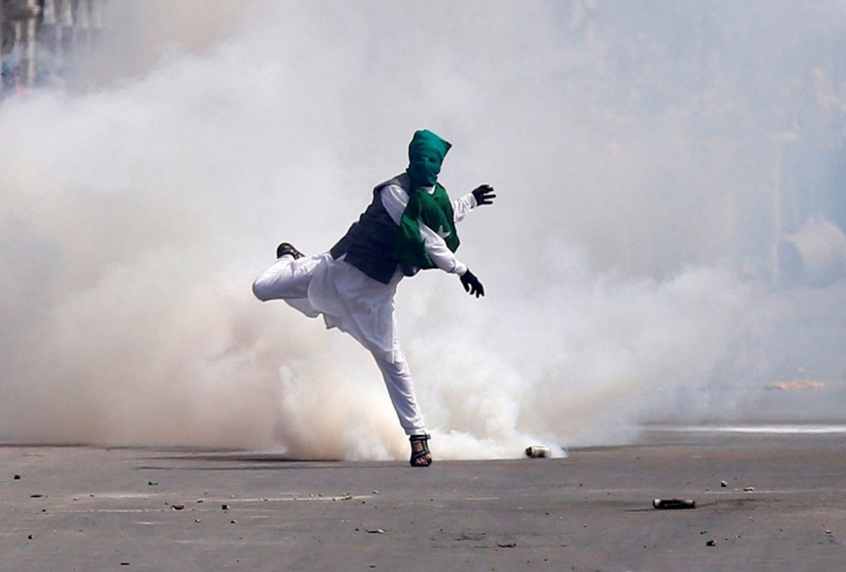 A demonstrator throws stones amid tear gas smoke fired by Indian police during a protest against what protesters say is the house arrest of Kashmiri separatist leaders, after Eid al-Fitr prayers in Srinagar July 6, 2016. REUTERS/Danish Ismail