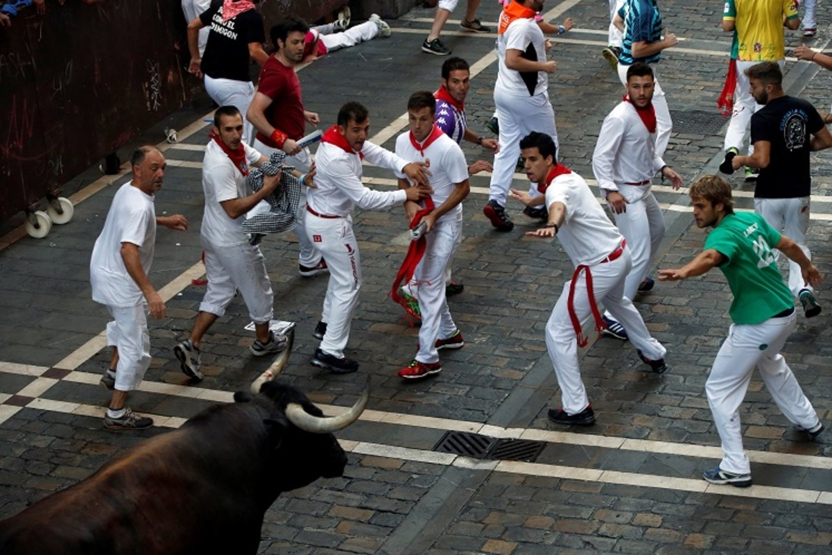 Runners try to lead a Cebada Gago ranch bull that turned around on Estafeta street during the second running of the bulls at the San Fermin festival in Pamplona, northern Spain July 8, 2016. REUTERS/Susana Vera