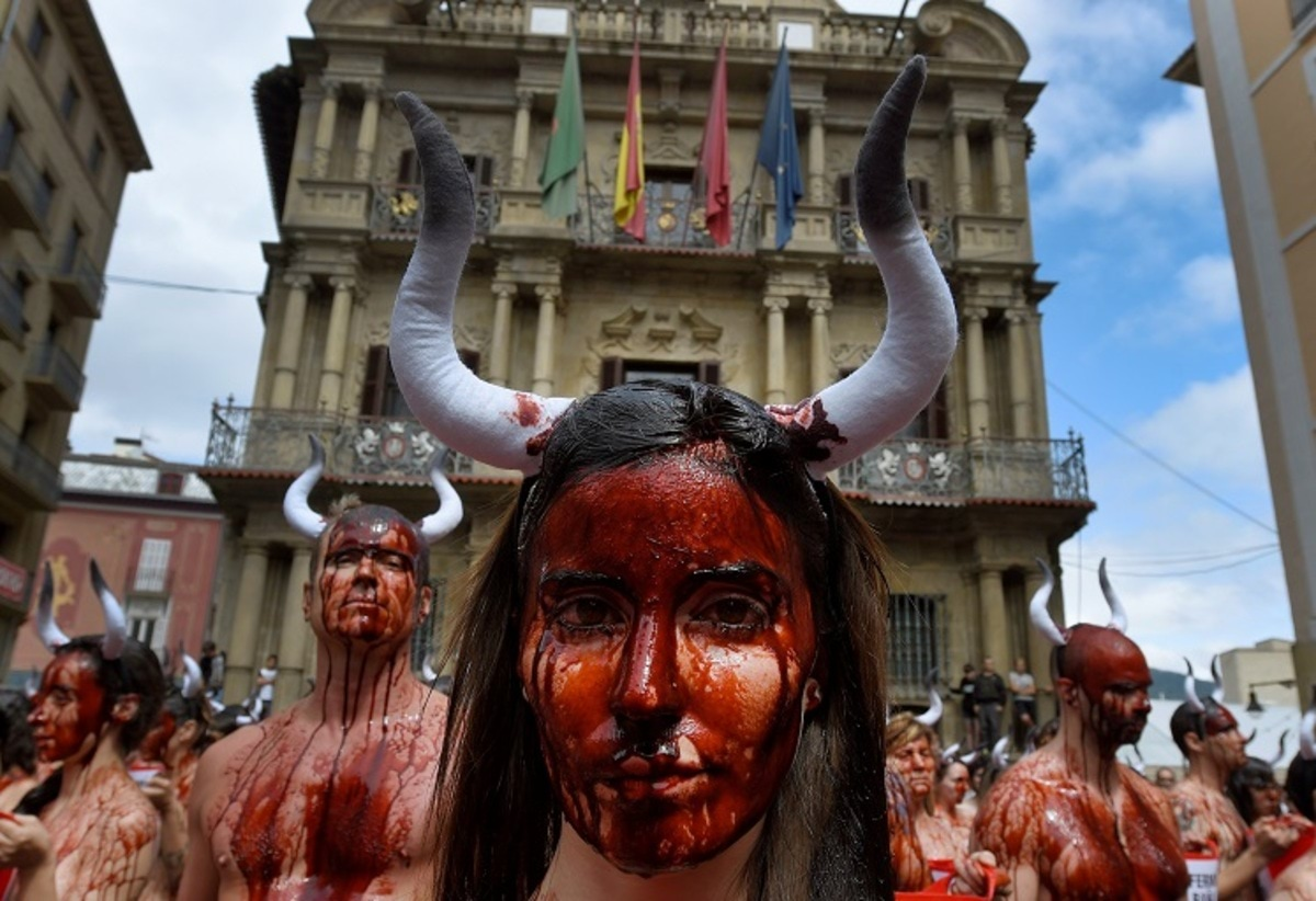 Animal rights protesters covered in fake blood demonstrate for the abolition of bull runs and bullfights a day before the start of the famous running of the bulls San Fermin festival in Pamplona, northern Spain, July 5, 2016. REUTERS/Eloy Alonso