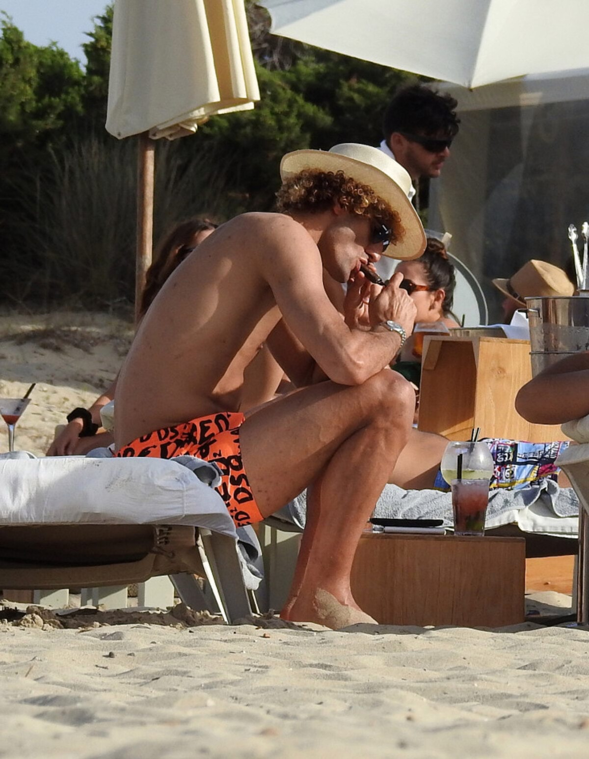 """EXCLUSIVE: Manchester United flop Marouane Fellaini puffs on a giant cigar - just days after Belgium were dumped out of Euro 2016 by Wales. The Belgian star, 28, was spotted relaxing on holiday in Ibiza with twin brother Mansour. An onlooker said: """"He didn't look like he had a care in the world."""" The group enjoyed drinks in the sunshine yesterday (July 4) surrounded by bikini-clad girls. Fellaini - in sunglasses and a hat - was seen knocking back what appeared to be cocktails and posing for photos with a fan. Pre-tournament favourites Belgium were knocked out of the competition after losing to Wales 3-1 on July 1. Fellaini has struggled to meet expectations at Old Trafford since signing with the club in the summer of 2013. Pics taken July 4th."""