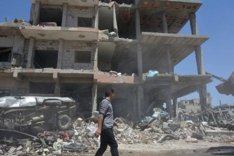 A man walks at a damaged site after two bomb blasts claimed by Islamic State hit the northeastern Syrian city of Qamishli near the Turkish border, Syria July 27, 2016. REUTERS/Rodi Said