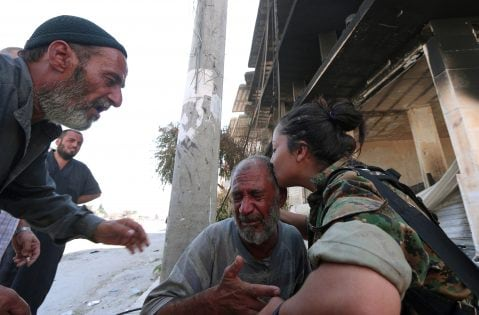 A Syria Democratic Forces (SDF) fighter comforts a civilian who was evacuated with others by the SDF from an Islamic State-controlled neighbourhood of Manbij, in Aleppo Governorate, Syria, August 12, 2016. The SDF has said Islamic State was using civilians as human shields. REUTERS/Rodi Said TPX IMAGES OF THE DAY