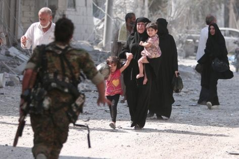 A Syria Democratic Forces (SDF) fighter rushes to help civilians who were evacuated by the SDF from an Islamic State-controlled neighbourhood of Manbij, in Aleppo Governorate, Syria, August 12, 2016. The SDF has said Islamic State was using civilians as human shields. REUTERS/Rodi Said