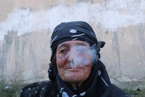 A woman smokes as she rests after she was evacuated with others by the Syria Democratic Forces (SDF) fighters from an Islamic State-controlled neighbourhood of Manbij, in Aleppo Governorate, Syria, August 12, 2016. The SDF has said Islamic State was using civilians as human shields. REUTERS/Rodi Said