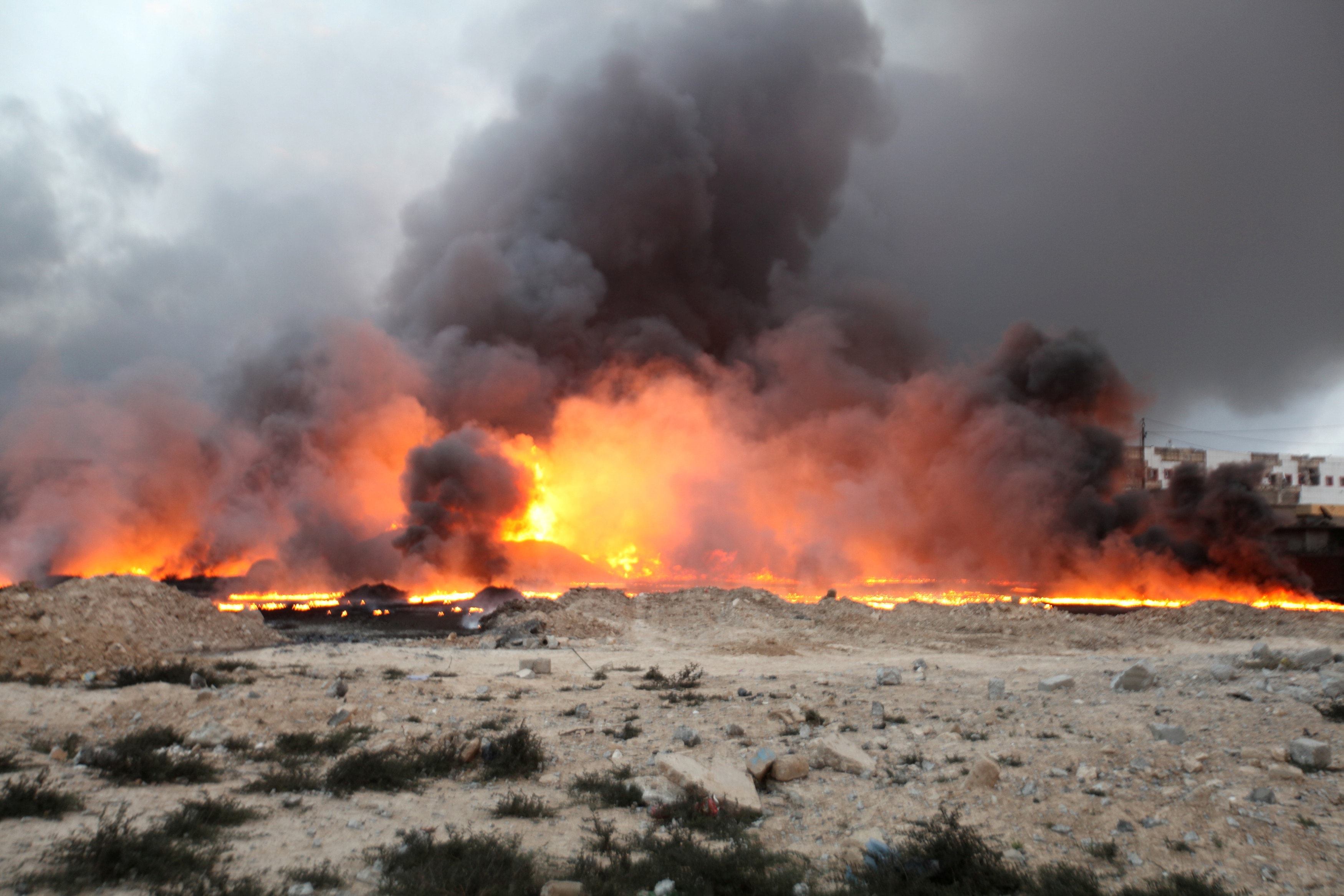 Fire rises from oil wells, set ablaze by Islamic State militants before fleeing the oil-producing region of Qayyara