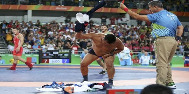 2016 Rio Olympics - Wrestling - Final - Men's Freestyle 65 kg Bronze - Carioca Arena 2 - Rio de Janeiro, Brazil - 21/08/2016. The coach of Mandakhnaran Ganzorig (MGL) of Mongolia takes off his clothes as he protests after the match against Ikhtiyor Navruzov (UZB) of Uzbekistan. REUTERS/Toru Hanai TPX IMAGES OF THE DAY. FOR EDITORIAL USE ONLY. NOT FOR SALE FOR MARKETING OR ADVERTISING CAMPAIGNS.