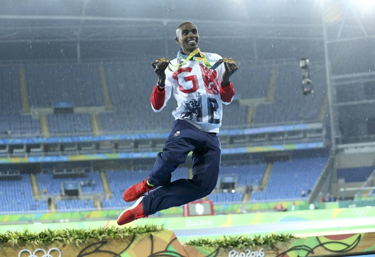 2016 Rio Olympics - Athletics - Final - Men's 5000m Final - Olympic Stadium - Rio de Janeiro, Brazil - 20/08/2016. Gold winner Mohamed Farah (GBR) of Britain celebrates and dances in the rain. REUTERS/Stoyan Nenov FOR EDITORIAL USE ONLY. NOT FOR SALE FOR MARKETING OR ADVERTISING CAMPAIGNS.
