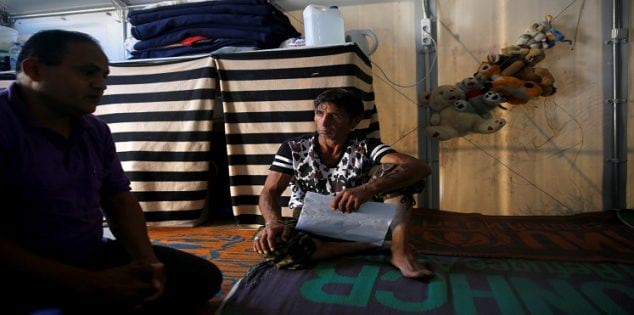 Syrian refugee Daud, 45, holds his registration papers inside his family's tent at the Souda municipality-run camp on the island of Chios, Greece, September 7, 2016. Picture taken September 7, 2016. To match EUROPE-MIGRANTS/CHIOS REUTERS/Alkis Konstantinidis