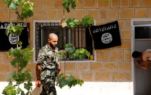 A member of Turkish-backed Free Syrian Army (FSA), seen with the Islamic State flags in the background, walks outside of a building in the border town of Jarablus, Syria, August 31, 2016. REUTERS/Umit Bektas