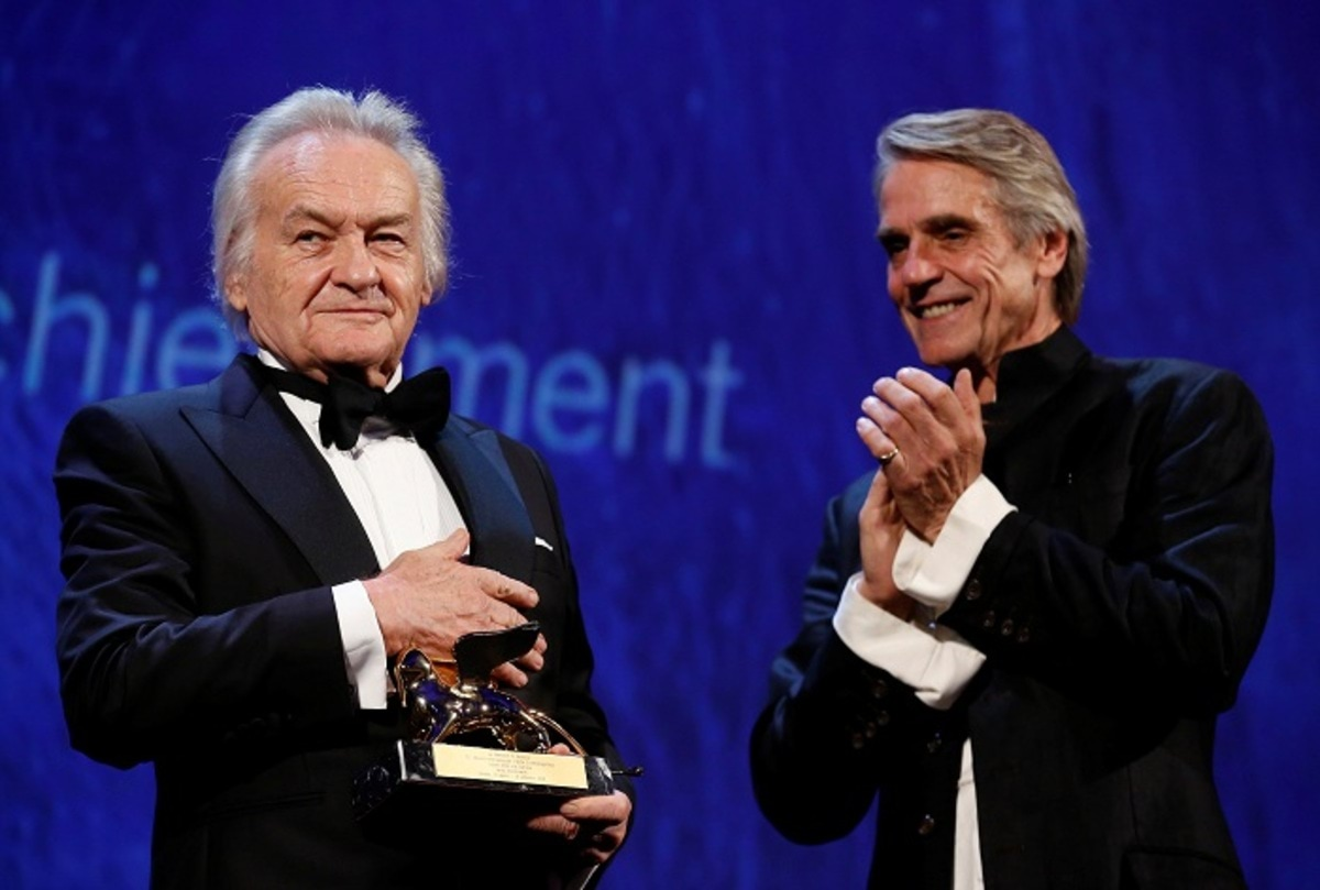 Director Jerzy Skolimowski holds his Golden Lion award for lifetime achievement next to actor Jeremy Irons during an opening ceremony of the 73rd Venice Film Festival in Venice