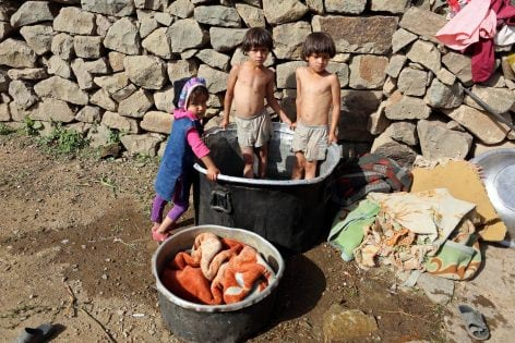 """Children stand in a tub where their mothers wash clothes on Dhalamlam Mountain, in the Jafariya district of the western province of Raymah, Yemen June 1, 2016. REUTERS/Abduljabbar Zeyad SEARCH """"MOUNTAINTOP"""" FOR THIS STORY. SEARCH """"WIDER IMAGE"""" FOR ALL STORIES."""