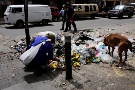 A man searches through garbage for food and recyclable materials near a supermarket in Caracas