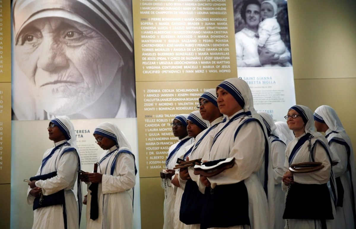 Members of Mother Teresa's order, the Missionaries of Charity, stand under a photograph before the unveiling of an official canonization portrait at the John Paul II National Shrine in Washington, U.S., September 1, 2016. REUTERS/Gary Cameron