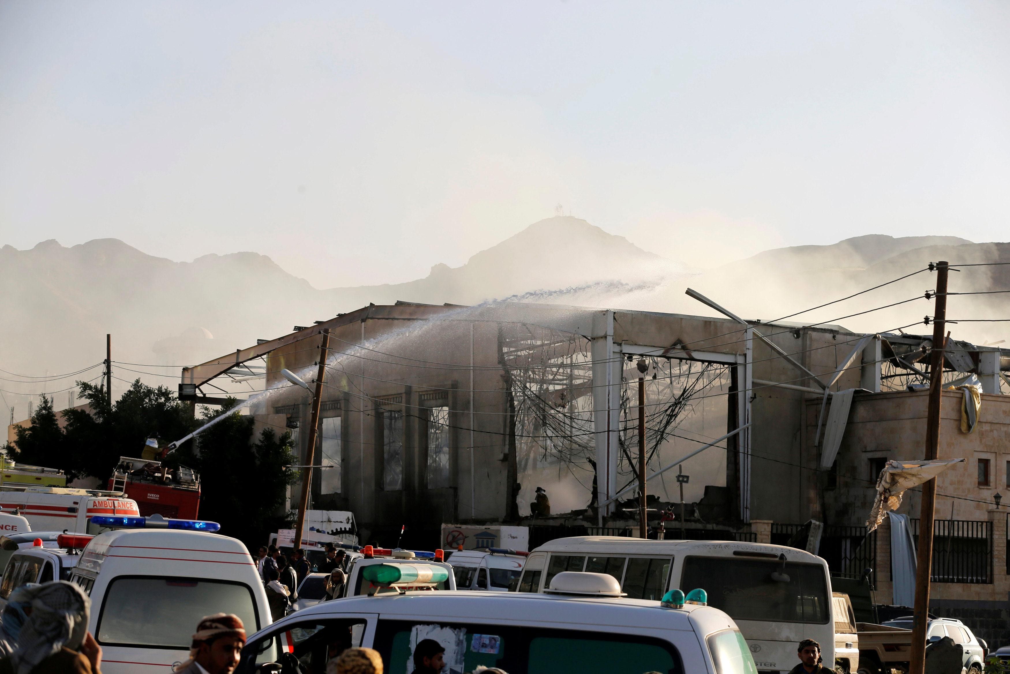 A fire engine sprays water on a damaged building at the site of an airstrike which witnesses said was by Saudi-led coalition aircraft on mourners at a hall where a wake for the father of Jalal al-Roweishan, the interior minister in the Houthi-dominated Yemeni government, was being held, in Sanaa, Yemen October 8, 2016. REUTERS/Khaled Abdullah
