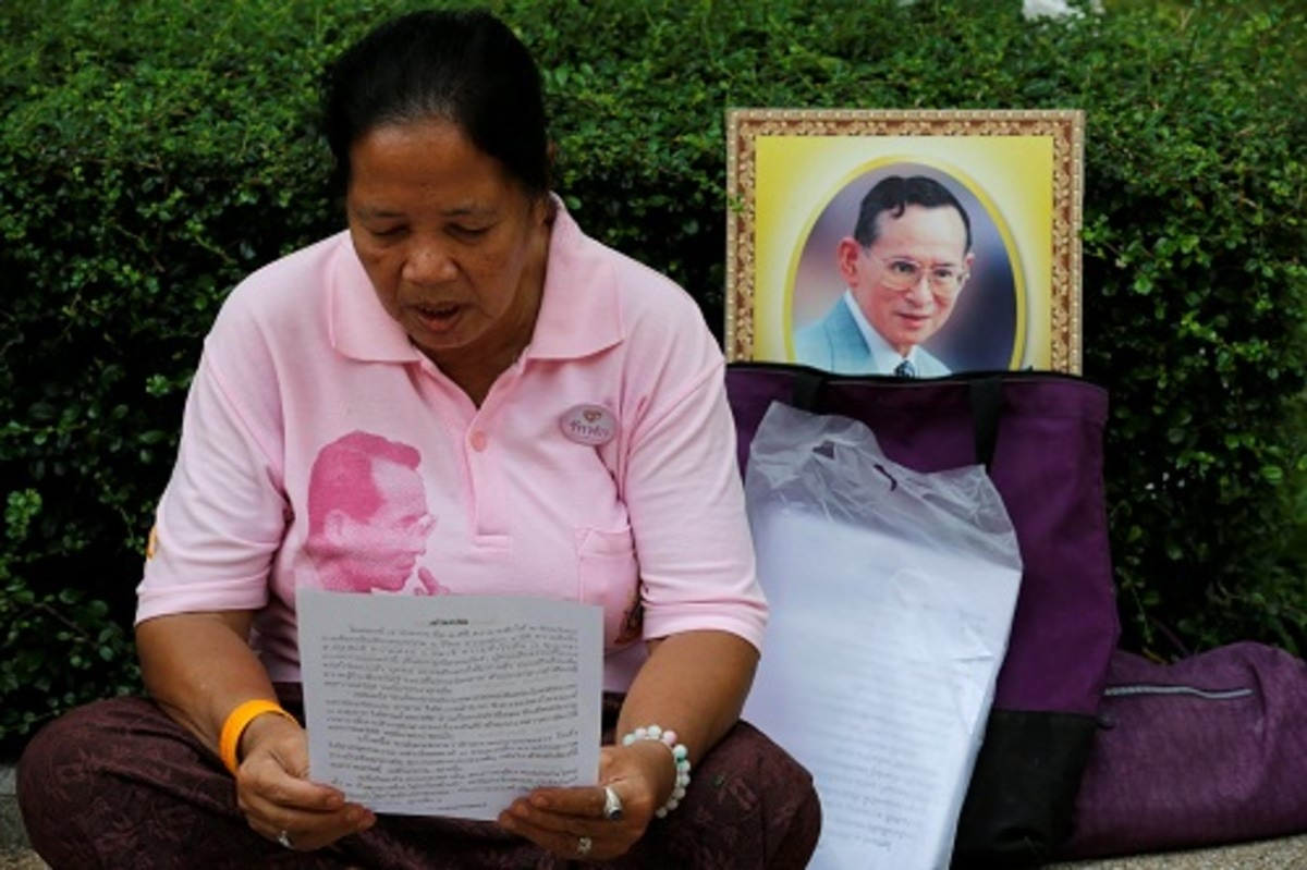 A well-wisher wears a pink shirt as she prays in front of a portrait of Thailand's King Bhumibol Adulyadej at Siriraj Hospital in Bangkok