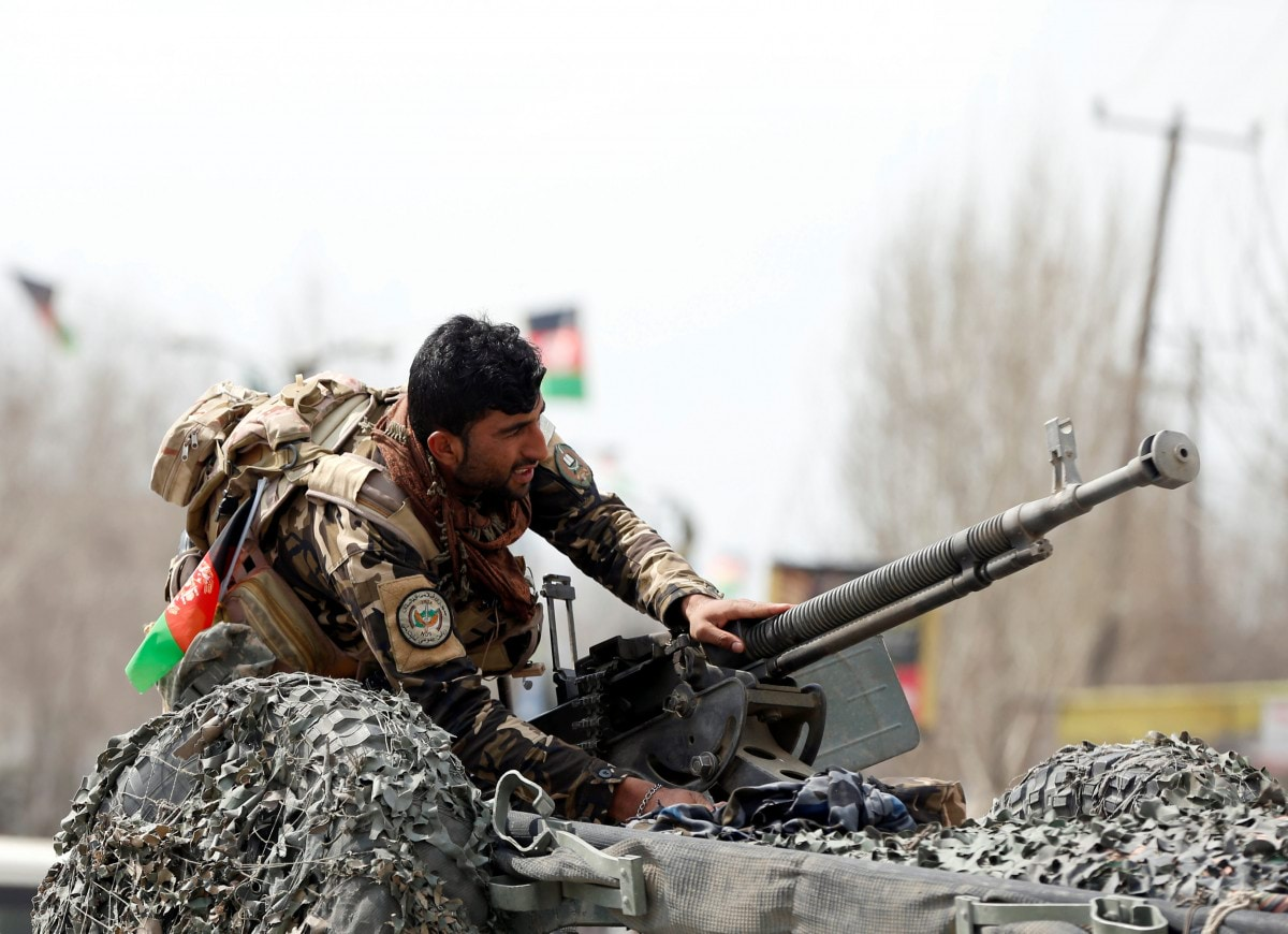 a-member-of-the-afghan-security-forces-prepares-his-machine-gun-at-the-site-of-a-suicide-bomb-attack-near-a-shiite-mosque-in-kabul